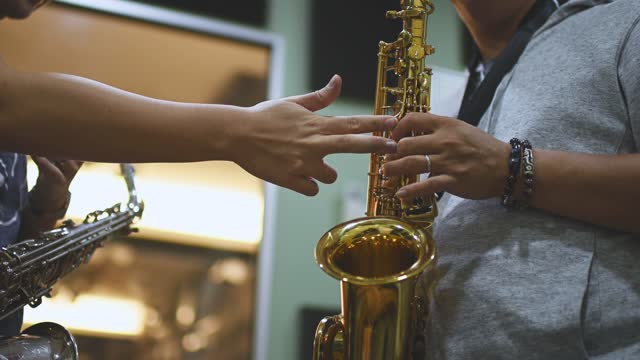 low angle close up Asian chinese mid adult man learning music instrument playing saxophone from his instructor in music studio