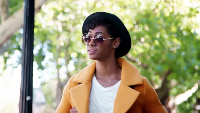 stockvideo's en b-roll-footage met lage hoek close up van een modieuze jonge zwarte vrouw het dragen van een hoed, zonnebril en een gele jas lopen in de straat, het hoofd en de schouders - street style