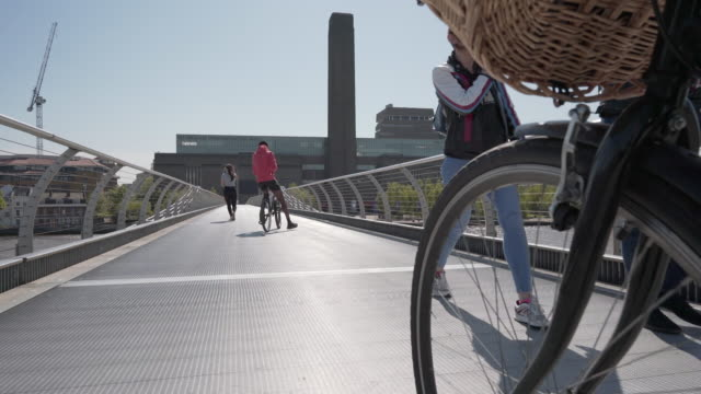 A low angle dolly shot with bicycle wheel over the Millennium footbridge towards the Tate Modern, London