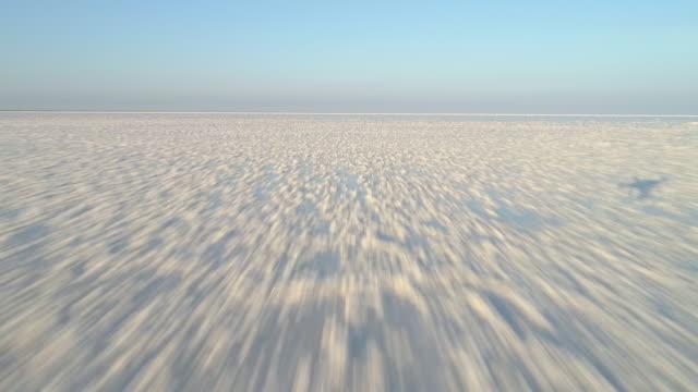 niedrigen winkel drone schnell fliegen nach vorne über den weißen salzsee mit einlagen von salz. luftaufnahme. - niedrig stock-videos und b-roll-filmmaterial