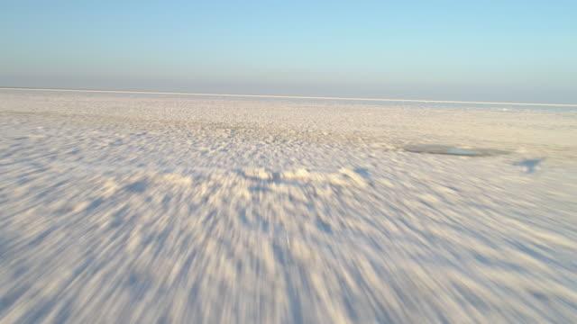 niedrigen winkel schnell fliegen über den weißen salzsee mit einlagen von salz. ersten punkt-view-modus. luftaufnahme. - niedrig stock-videos und b-roll-filmmaterial
