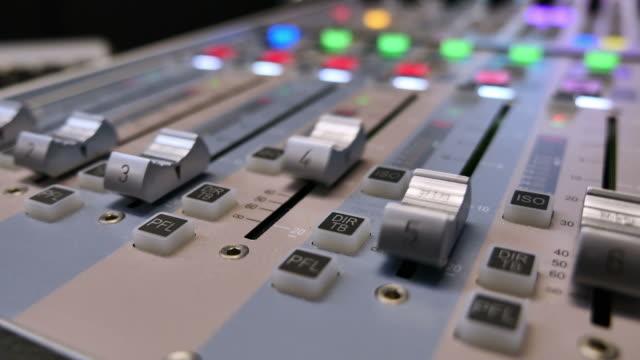 stockvideo's en b-roll-footage met lage hoek beelden van een audio-mixer en de knoppen automatisch omhoog en omlaag wordt getrokken - infaden