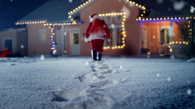 vídeos de stock e filmes b-roll de low angle footage of santa claus with red bag, walks into front yard of the idyllic house decorated with lights and garlands. santa bringing gifts and presents at night. magical new year's eve with falling snow. - pai natal