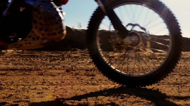 Low Angle Footage of Spinning Wheels of FMX Dirt Bike Driving on the Sand Track Past the Camera. video