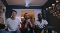 istock Low angle happy multiethnic young friends watch football game together at home with drinks using projector slow motion. 1189351720