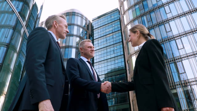 Low angle, hiring young motivated woman for a project, two businessmen negotiators wear suits shake hands with intern after successful negotiations, seller banker handshake deal agreement concept