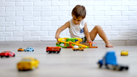 vídeos de stock e filmes b-roll de low angle little caucasian boy playing with cars on the floor, 4k - brinquedo