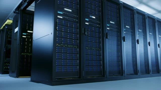 niedrigen winkel aufnahme des rechenzentrums mit mehreren reihen von voll funktionsfähigen server-racks bewegen. moderne telekommunikation, cloud-computing, künstliche intelligenz, datenbank, supercomputer-technologie-konzept. - netzwerkserver stock-videos und b-roll-filmmaterial