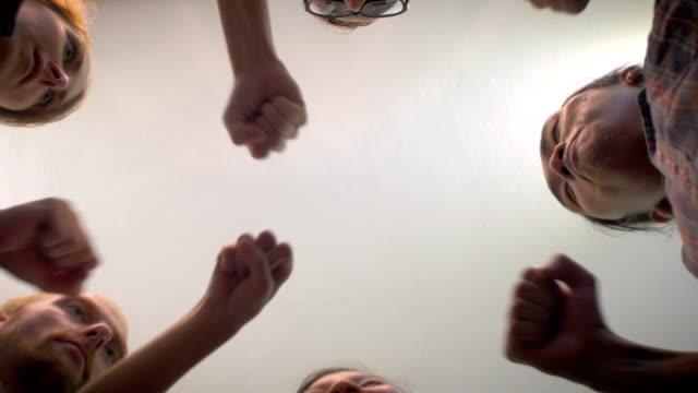 stockvideo's en b-roll-footage met lage hoek van 5 jonge millennials passen bult met hun handen in een cirkel - aziatische etniciteit