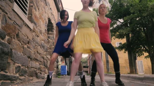 låg vinkel av en hip hop dans rutin som utförs av tre kvinnor i en gränd - blue yellow band bildbanksvideor och videomaterial från bakom kulisserna