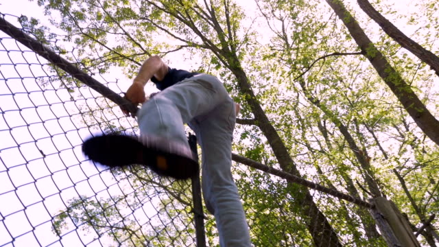 vídeos de stock e filmes b-roll de low angle of a man climbing over a chain link fence trespassing in slow motion - cercado