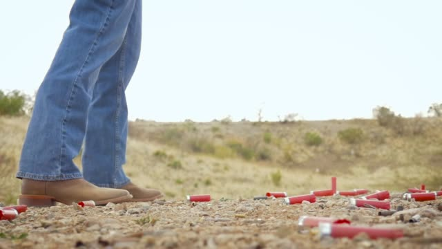 Low Angle of a Man in Cowboy Boots Shooting a Shotgun