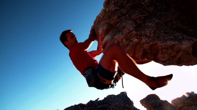 vídeos y material grabado en eventos de stock de vista de ángulo bajo de extrema escalada libre hombre colgante en roca - escalada en rocas