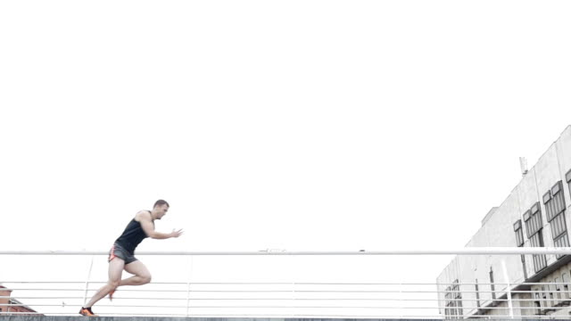 Low angle of strong-willed athlete running quickly along the bridge video