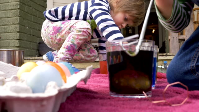 Low angle of two cute children dyeing easter eggs together in colored dye video