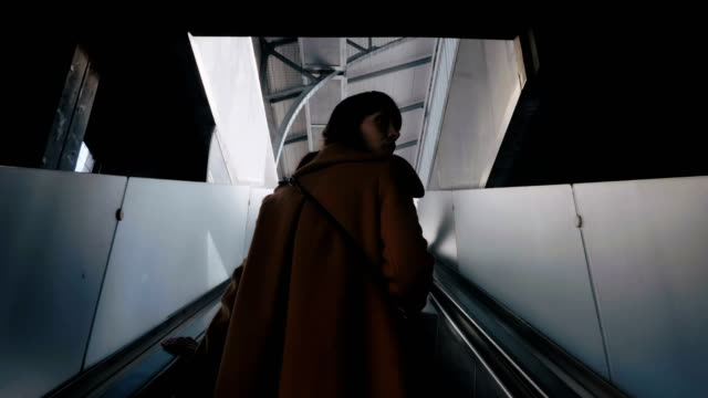 Low angle rear view young elegant tourist woman looks back riding modern escalator at a metro station slow motion. Low angle rear view young elegant tourist woman looks back riding modern escalator at a metro station slow motion. Transportation and modern architecture technology, businesswoman using public transit french architecture stock videos & royalty-free footage