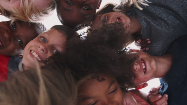 Low Angle Shot Looking Up Into Faces Of Children With Friends Smiling Into Camera Low angle portrait looking up into faces of children looking down into camera - shot in slow motion elementary age stock videos & royalty-free footage