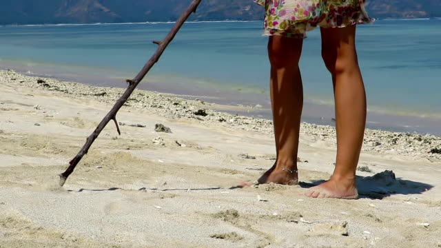 Low angle shot of a girl drawing shapes in sand Low angle shot of a girl drawing shapes in sand with tree branch in Gili Air island, Indonesia stick plant part stock videos & royalty-free footage