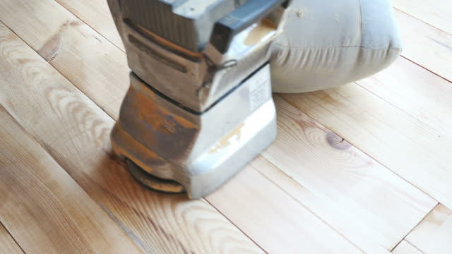 A low angle shot of a man sandering a parquet with a parquet sandering machine video