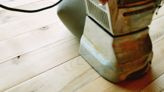 A low angle shot of a man sandering a parquet with a parquet sanding machine video