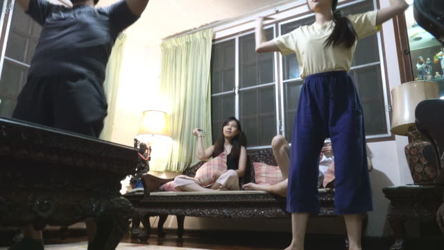 Low angle shot of Asian family working out in living room