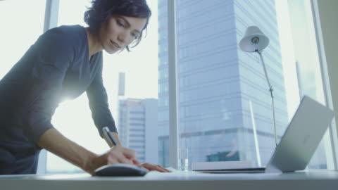 vídeos y material grabado en eventos de stock de tiro de ángulo bajo de confianza empresaria se inclina sobre su escritorio de oficina, escribe información en documentos y se ve en el portátil. exitosa mujer de negocios. - escritorio