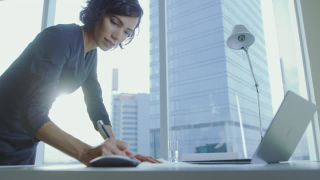 low angle shot of confident businesswoman leans on her office desk, writes down information in documents and looks at laptop. successful woman doing business. - scrivania video stock e b–roll