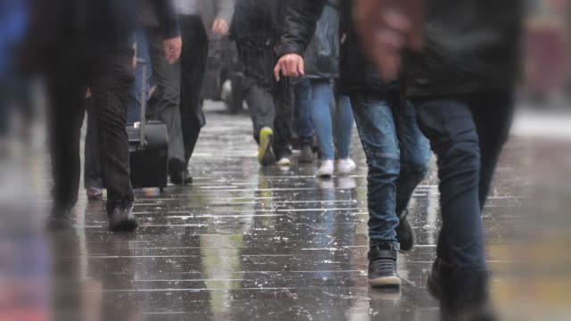 Low angle shot of feet walking in the rain.