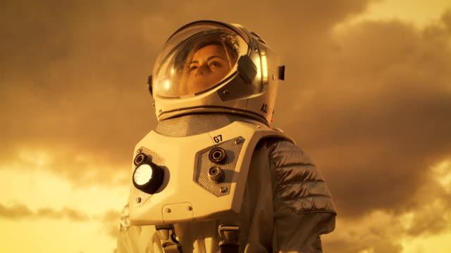 Tiro de ángulo bajo de mujer astronauta en el traje espacial, mirando a su alrededor planeta alienígena. Planeta rojo y el naranja Similar a Marte. Tecnologías avanzadas, recorrido de espacio, concepto de colonización. - vídeo