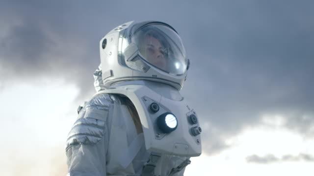 Tiro de ángulo bajo de mujer astronauta en el traje espacial, mirando a su alrededor planeta alienígena. Planeta azul y fría. Tecnologías avanzadas, recorrido de espacio, concepto de colonización. - vídeo