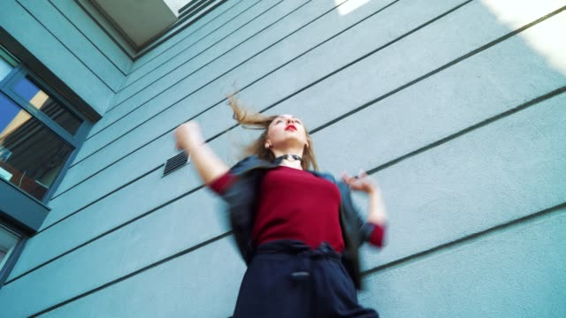 low angle shot of female street dancer performing near modern building in sunset - top nero video stock e b–roll
