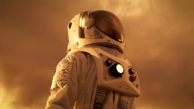 low angle shot of the brave astronaut in the space suit looking around alien planet. red and orange planet similar to mars. advanced technologies, space travel, colonization concept. - space exploration stock videos & royalty-free footage