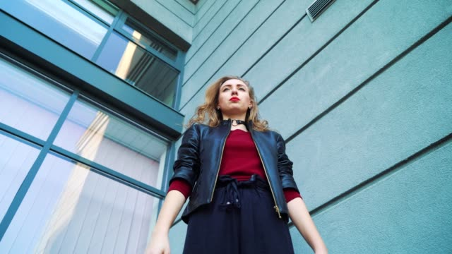 low angle shot of young blonde woman standing against building and gesturing - top nero video stock e b–roll