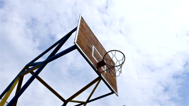 Low angle time lapse of basketball hoop enlightened by the morning sun video