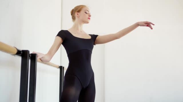 low-winkel-tracking-aufnahme von eleganten jungen ballerina in schwarzem trikot und spitzenschuhe machen übung bei barre im ballettstudio - gymnastikanzug stock-videos und b-roll-filmmaterial