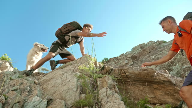 Low angle video of Son helping out his father climbing a rock while hiking at mountain