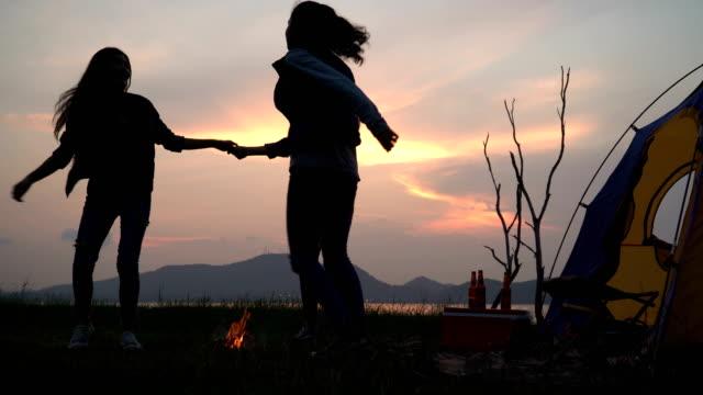 düşük açı görünümü: arkadaş yaz aylarında kamp ateşi etrafında dans ederken günbatımı göl yakınında kamp yaparken - şenlik ateşi stok videoları ve detay görüntü çekimi