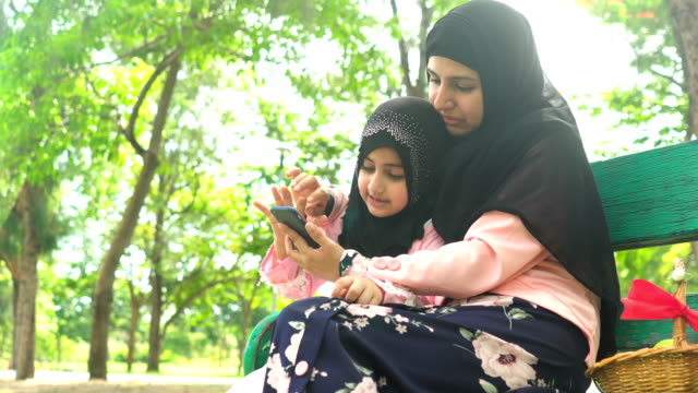 low angle view: Muslim girl using smartphone with her mother on bench in public park in morning
