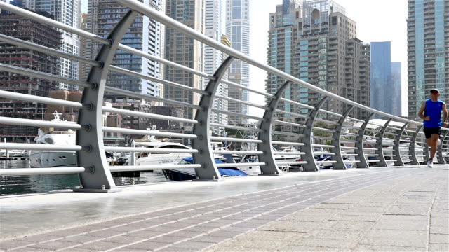 Low angle view of athletic fitness man running jogging in Dubai Marina in the morning, slow motion video