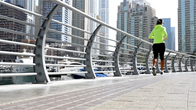 Low angle view of athletic fitness woman running jogging in Dubai Marina in the morning, slow motion video