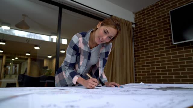 vidéos et rushes de vue faible angle de belle femme travaillant sur un plan d'affaires à la recherche très ciblée - vue en contre plongée