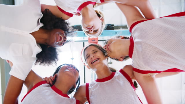 low angle view of female high school basketball players having team talk with coach - bambine femmine video stock e b–roll