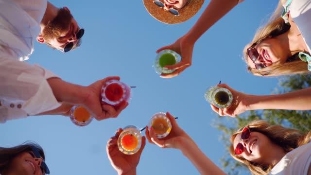 low-winkel-ansicht von freunden, die spaß an der pool-party haben, klinkengläser mit bunten sommercocktails in der nähe des hotelpools. menschen toasten frischen saft in luxus-sommervilla in zeitlupe - niedrig stock-videos und b-roll-filmmaterial