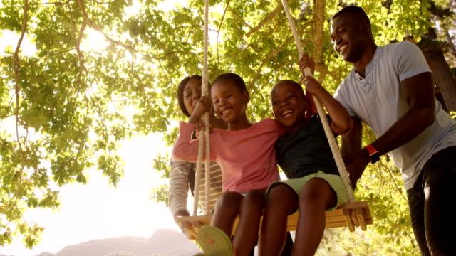 niedrigen winkel blick auf glückliche familie spielen auf der schaukel - schaukel stock-videos und b-roll-filmmaterial