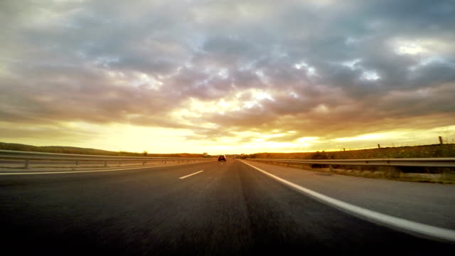 low angle view of highway drive toward the sunset, sunrise - lungo video stock e b–roll