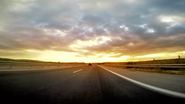 vídeos de stock e filmes b-roll de low angle view of highway drive toward the sunset, sunrise - reto descrição física