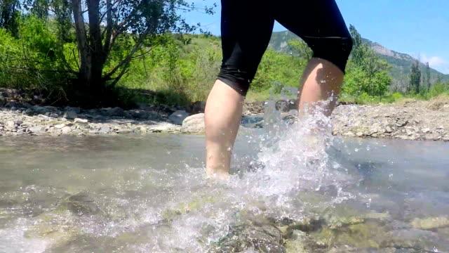 Low angle view of hiking woman on hike track crossing mountain creek creek video