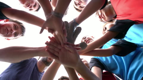 Low angle view of kids Football School Team huddling together Low angle view of kids Football School Team huddling together. They are putting hands together in circle. Sun beams, lens flare. childhood stock videos & royalty-free footage