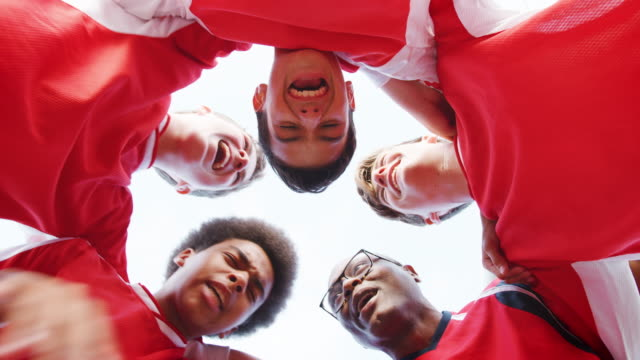 Low Angle View Of Male High School Soccer Team And Coach Having Team Talk Low angle view of male high school soccer team in huddle with coach and discussing tactics before joining hands - shot in slow motion high school sports stock videos & royalty-free footage