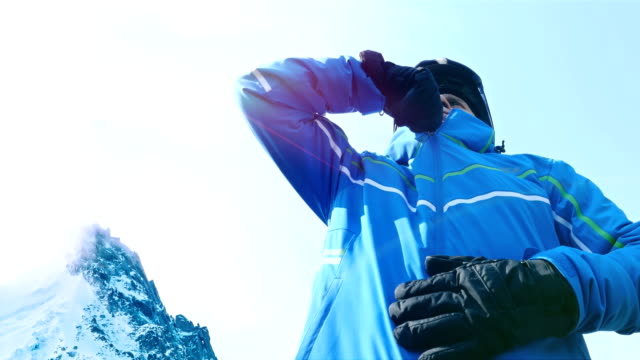 Low angle view of male skier putting his glasses on blue sky video